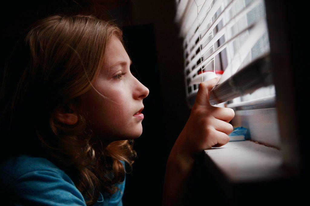 girl looks through window during quarantine
